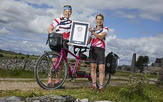 Two women in cycling kit stand either side of a pink tandem bicycle holding a framed certificate