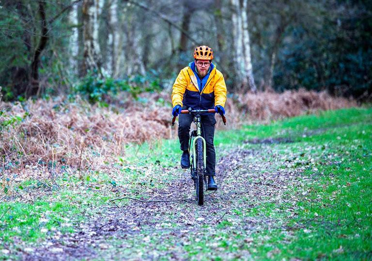 A cyclist wearing winter clothing cycles through a wood