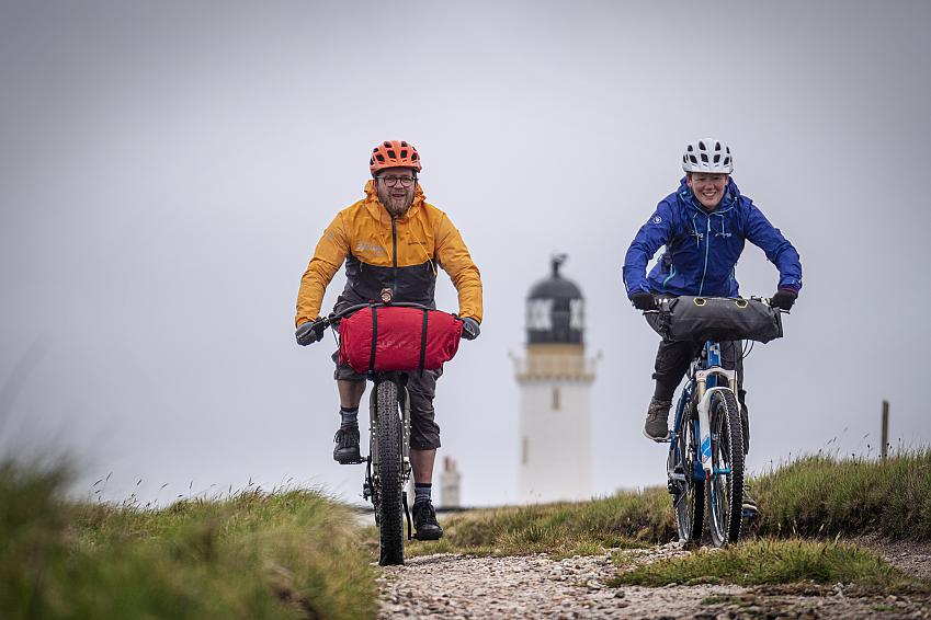 Two bikepackers cycling away from the lighthouse at Cape Wrath. Photo Robby Spanring