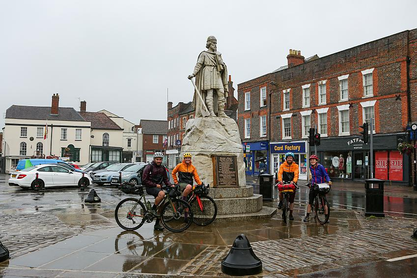 Four cyclists stand by the King Alfred memorial in Wantage.