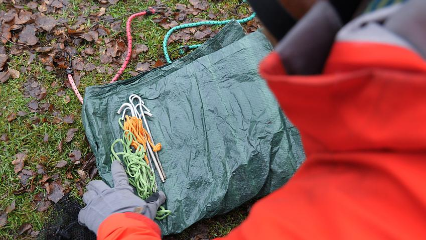 A tarp, paracord, pegs and bungees