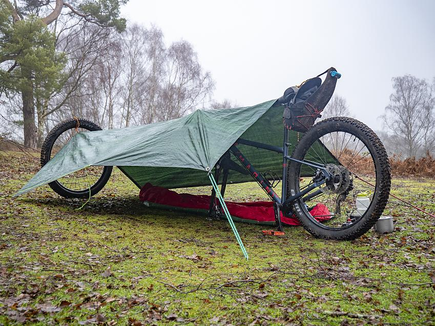 A single wheeled shelter is opened up by using the front wheel as a pole