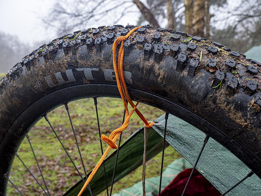 A bike wheel is used as a pole for a tarp.