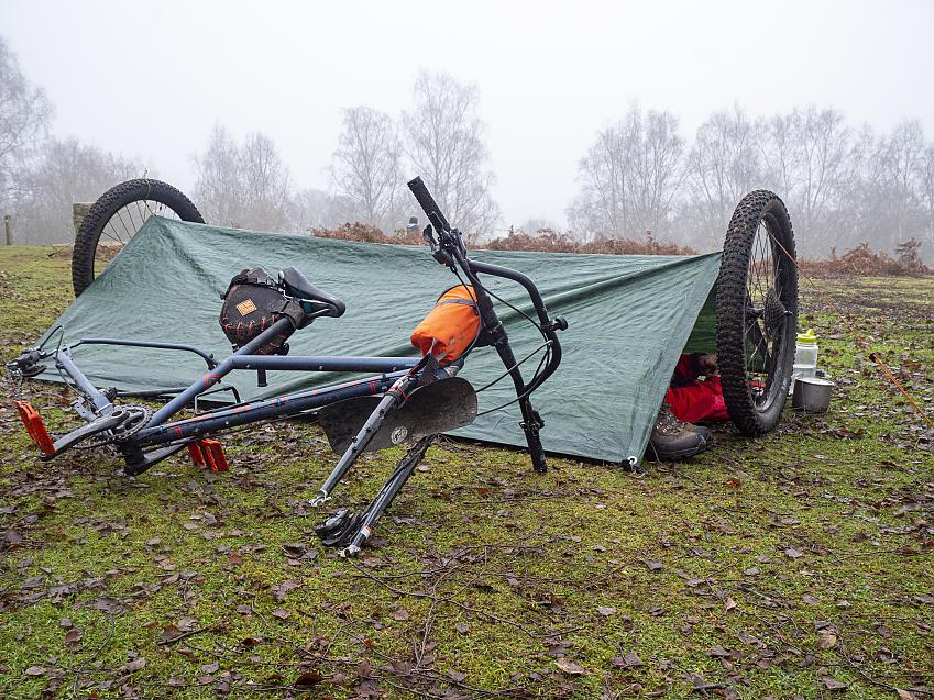 A shelter set up using a tarp and two bicycle wheels