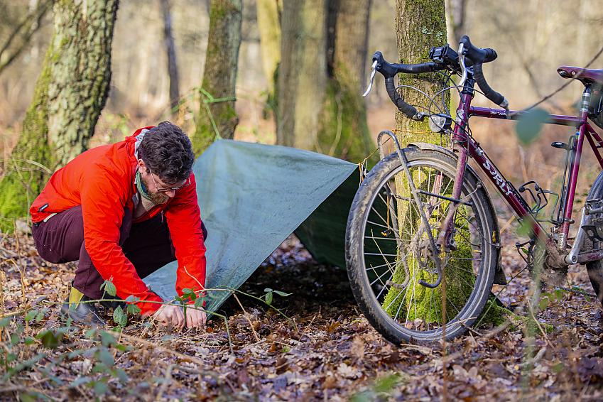 A man setting up a simple A-frame tarp between two trees