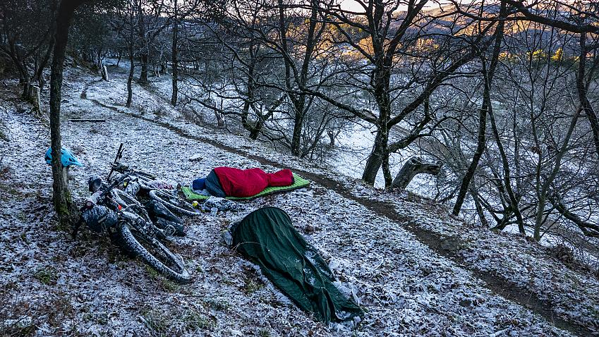 A wild campsite with two bikepackers bivvying dusted in snow