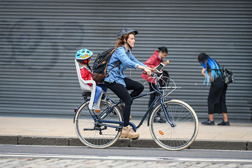 A woman rides a bicycle in Edinburgh with a child in a bike seat