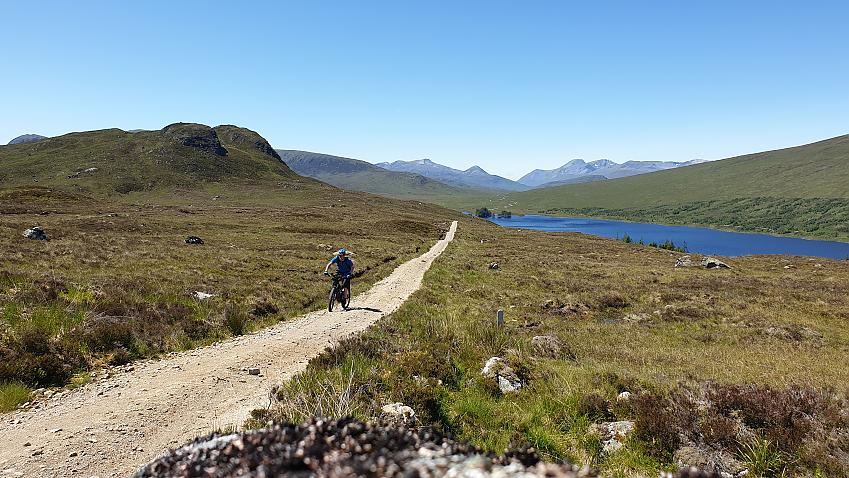 Cyclist on gravel track by lake
