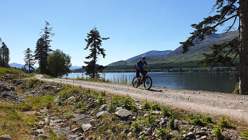 A man riding along a gravel track beside a loch