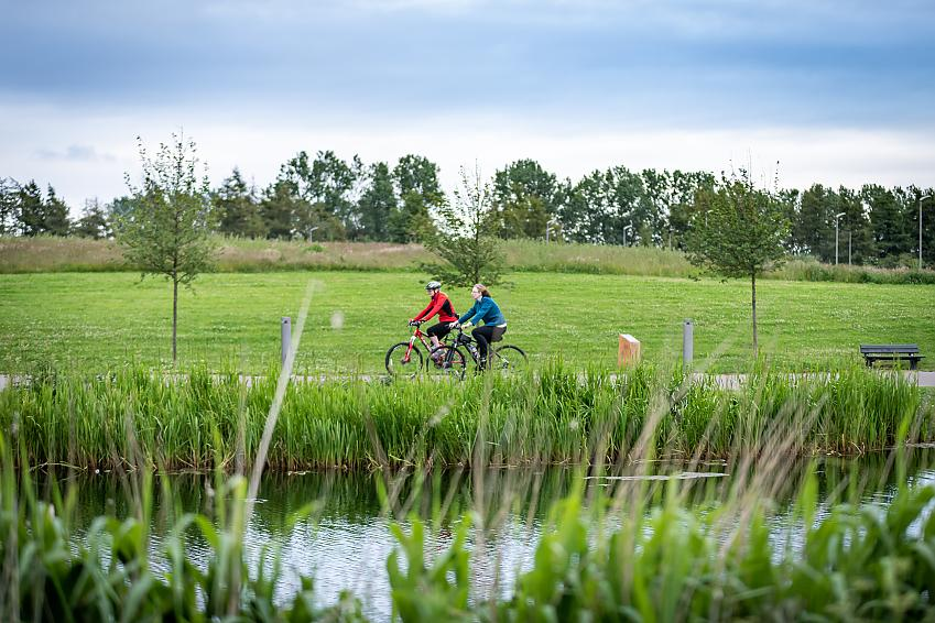 Two people riding bikes along a canal path