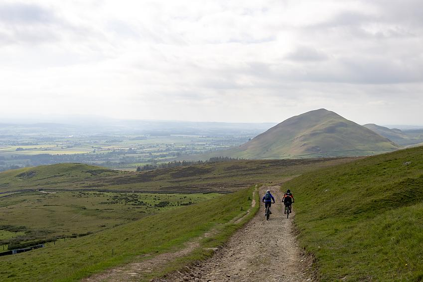 Two mountain bikers riding down a gravel track towards hills in the distance.
