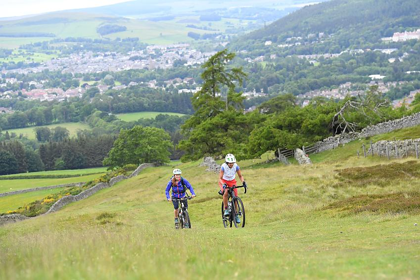 Two women riding up a grassy hill on mountain bikes