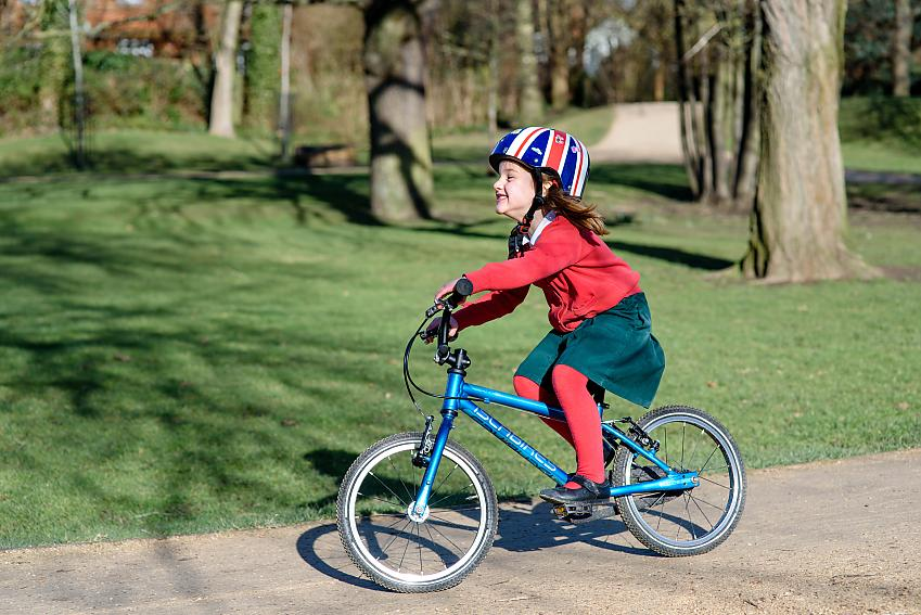 Girl smiling cycling through park
