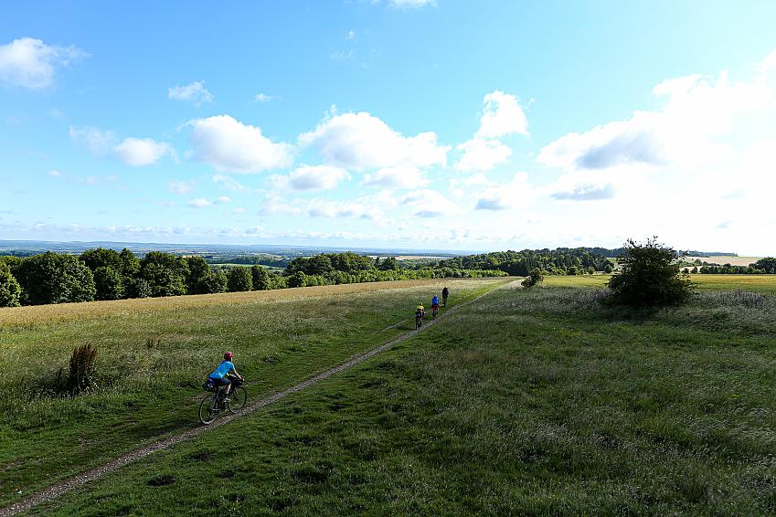 Four people cycle along a grassy track under a wide blue sky