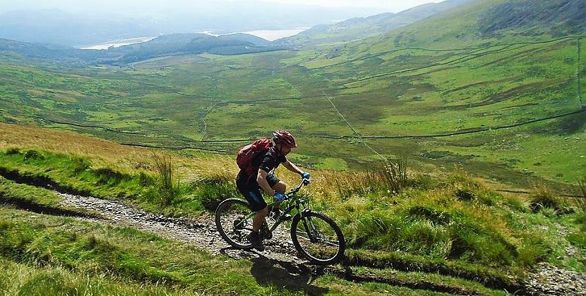 Mountain biker riding along gravel track past hills and lake