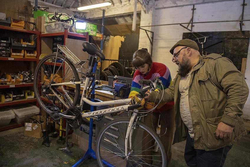 A man in a brown jacket and woman in rainbow woolly jumper working on a bike in a workshop