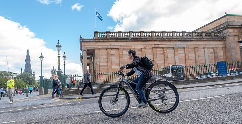 Woman cycling on a road in Edinburgh