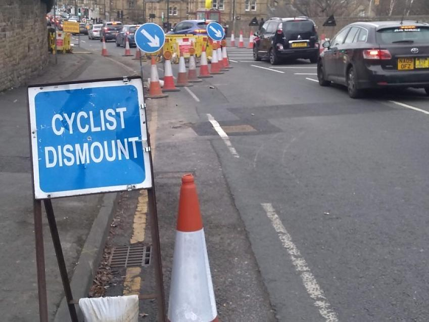 Cyclists dismount sign