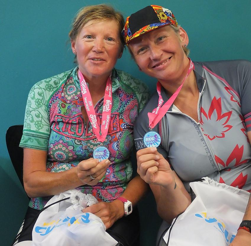 Two cyclists with medals and goodie bags. Photo by Graham Brodie