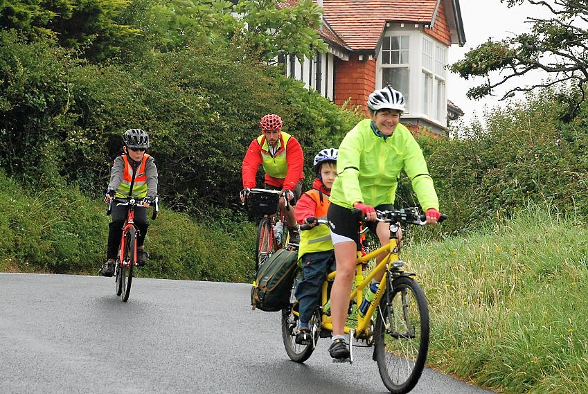 Family cyclists riding down a hill
