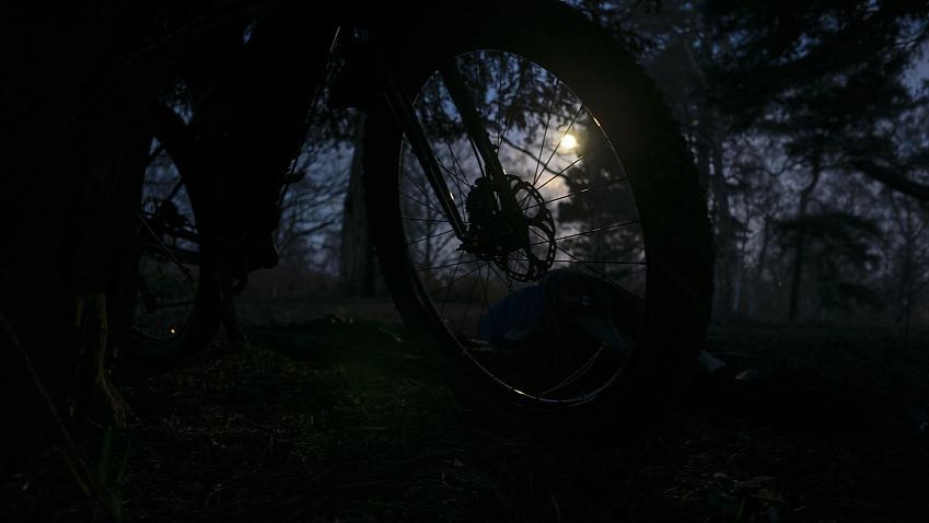 The full moon at dawn viewed through a bike wheel