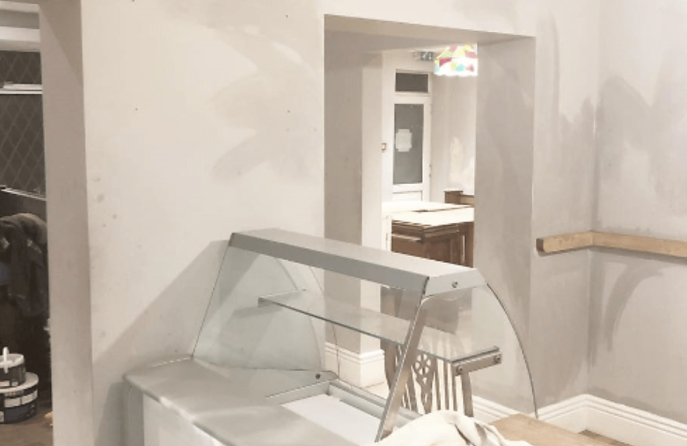 A newly painted serving counter in a cafe. No people are present the walls are white