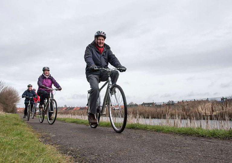 A community cycling club riding along a canal tow path