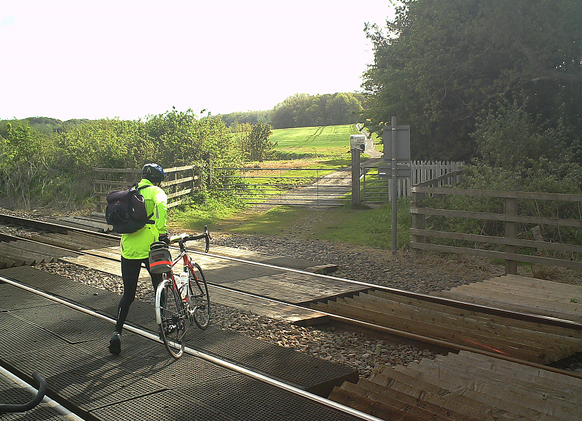 A cyclist pushes his bicycle across a level crossing.