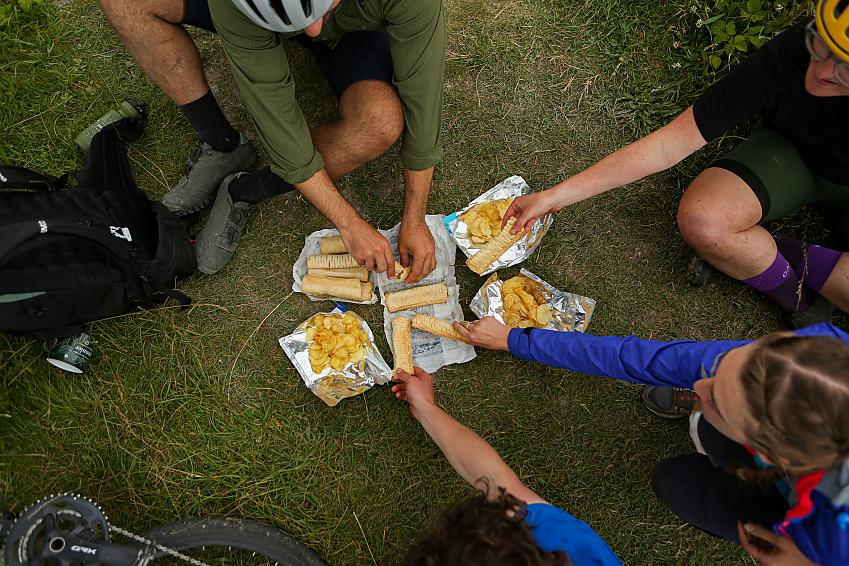 Cyclists dip into a healthy lunch of baked goods and crisps.
