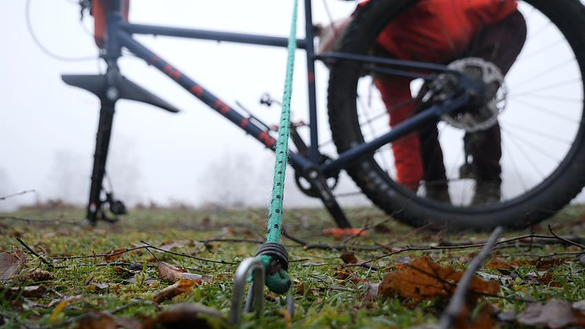A bicycle is fixed in an upright position using two bungee cords.