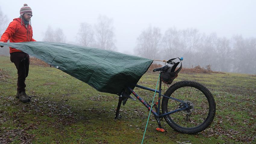 A man spreads his tarp over his bike before pegging it down