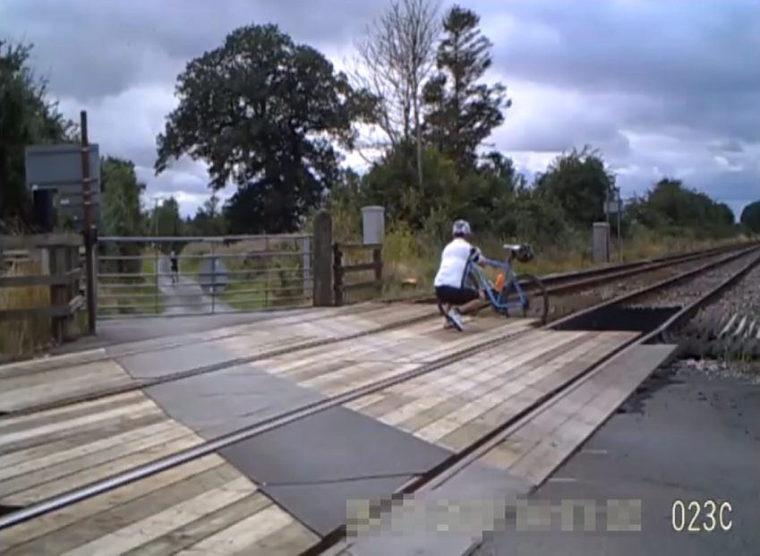 A cyclist taking a photo while on a level crossing