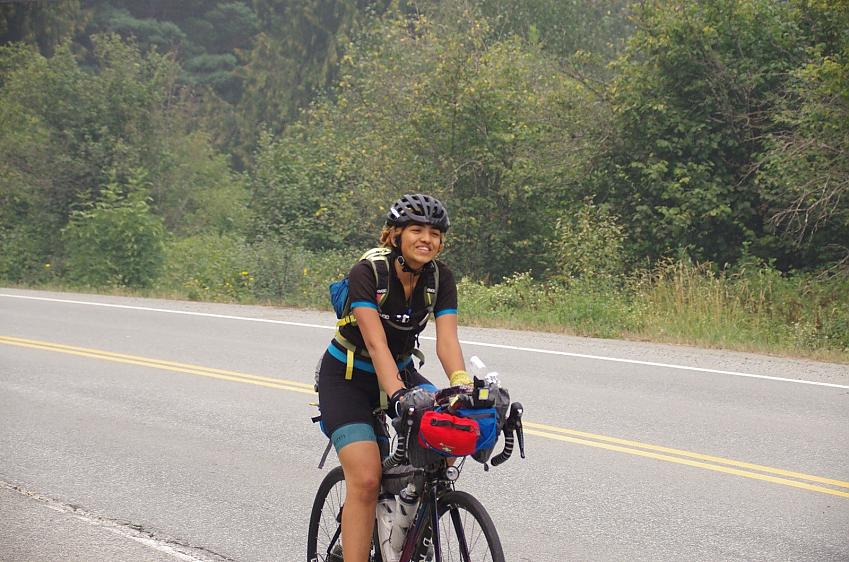 A woman cycles with a fully laden bikepacking set up