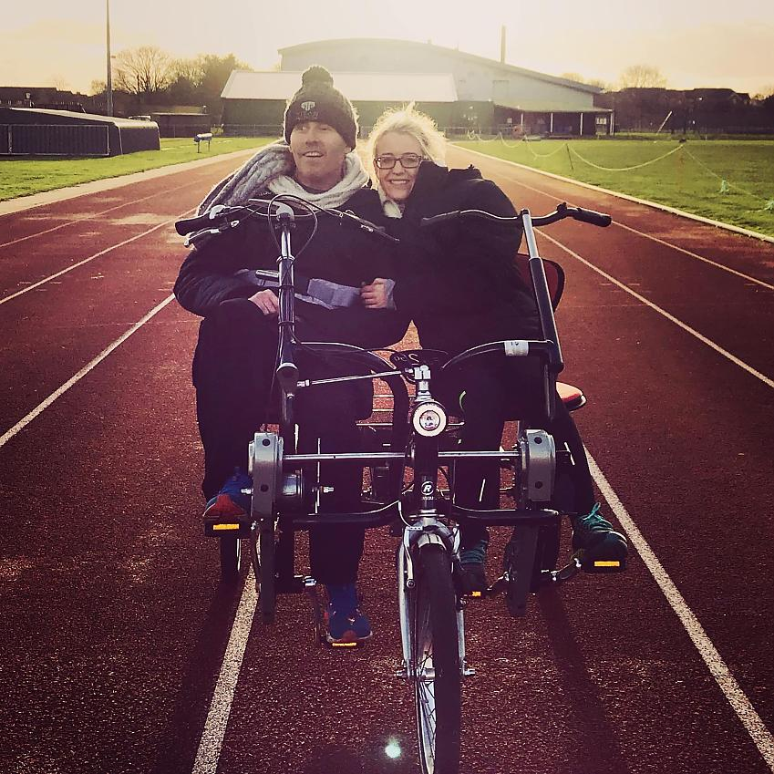 Colin with his partner Holly, using an adapted cycle. Colin's injuries mean he's no longer able to cycle unassisted. 2019
