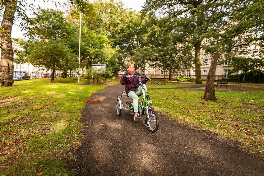 Susan Robertson riding a tricycle through a park
