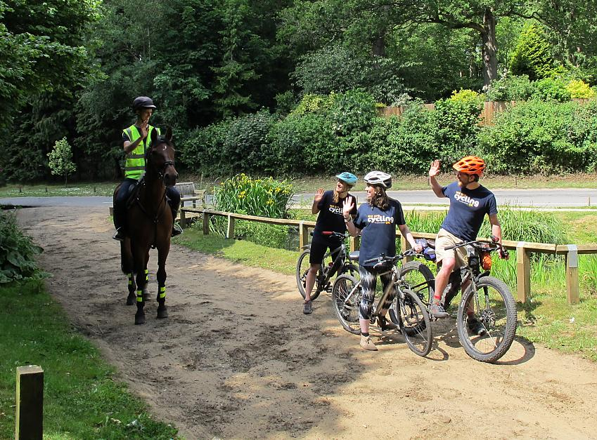 A horse rider smiles and waves at three cyclists who have moved over to the side of the path to let him pass