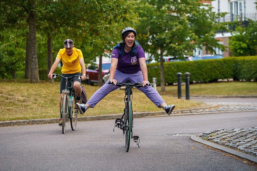 A smiling woman kicks her legs out while riding a bike