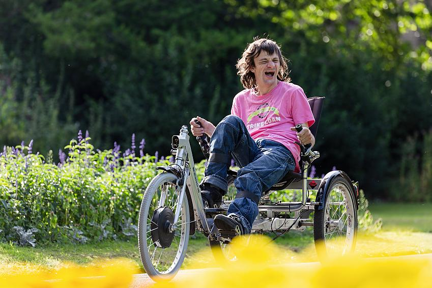 Man laughing as he rides an adapted tricycle
