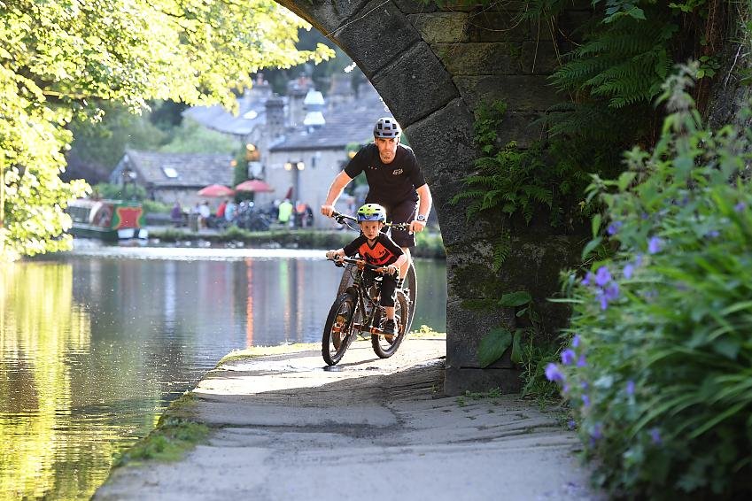 A man and young boy cycle under a bridge on a canal towpath