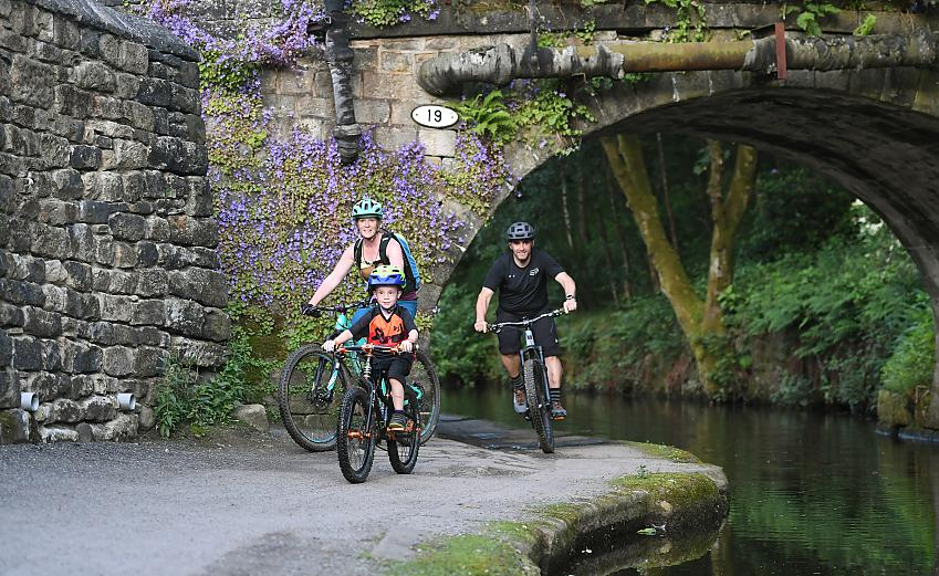 A family of three emerge from beneath an old stone bridge as they cycle along on an attractive canal towpath