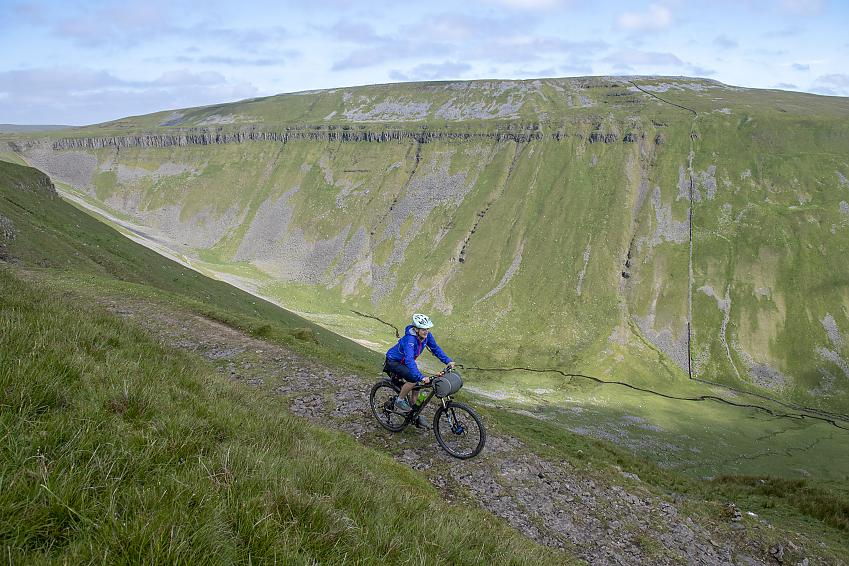 A mountain biker rides along a stony trail along the side of a dramatic valley at High Cup Nick, Cumbria