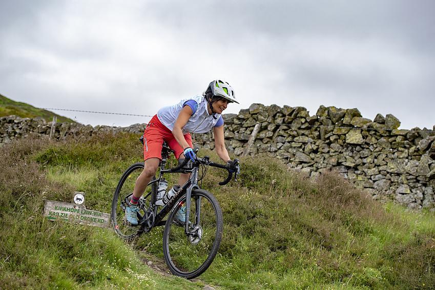Woman riding a gravel bike down a grassy trail