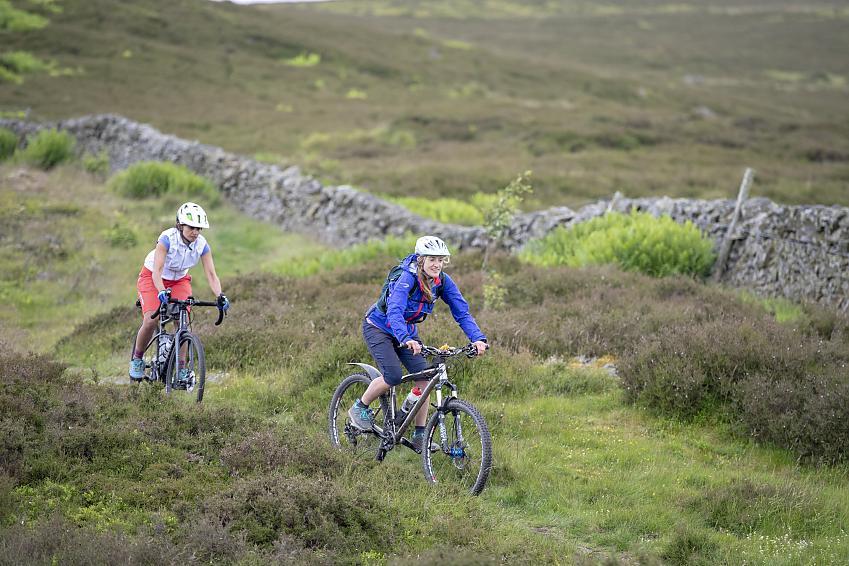 Two women mountain biking over heathery terrain