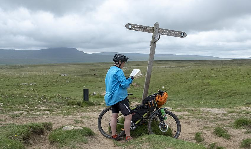 Woman with mountain bike looking at a map