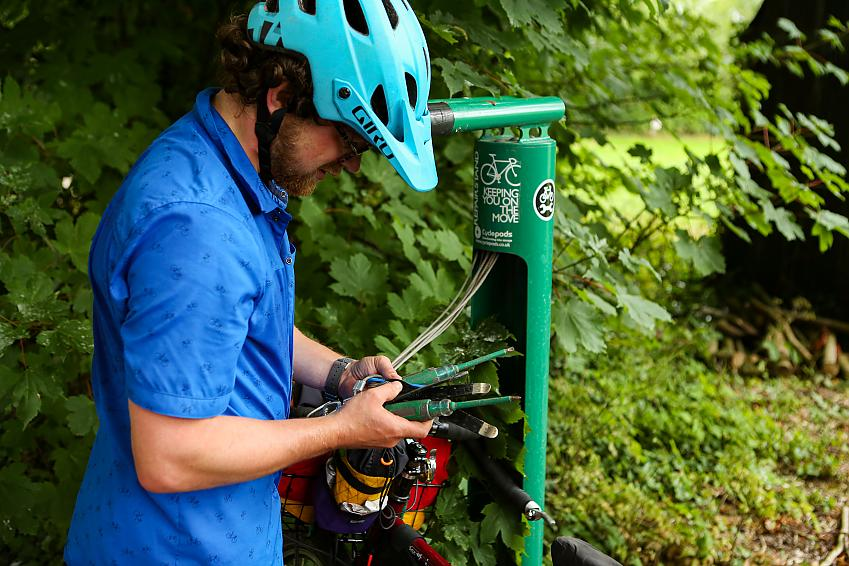 Cyclist using communal tools to fix bike