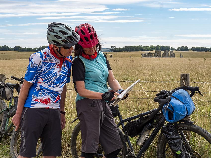 Two cyclists looking at a map with Stonehenge in the background