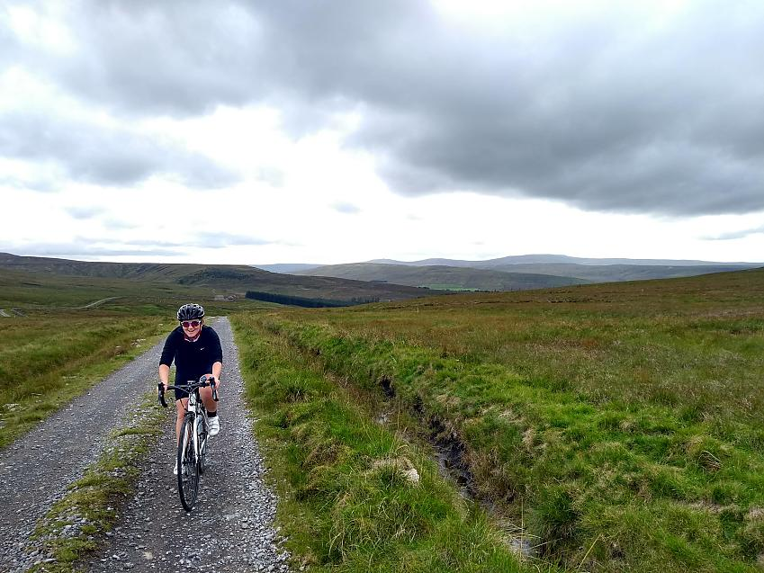 A woman cycles along a gravel track across rolling moorland