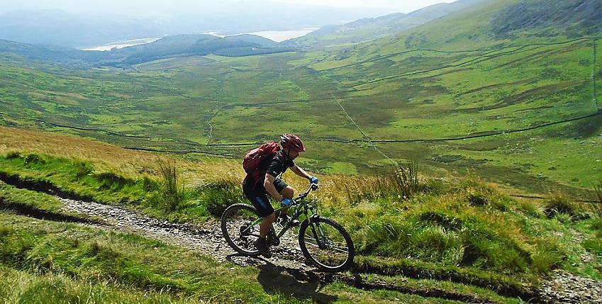 Mountain biker riding along gravel track past hills and lake