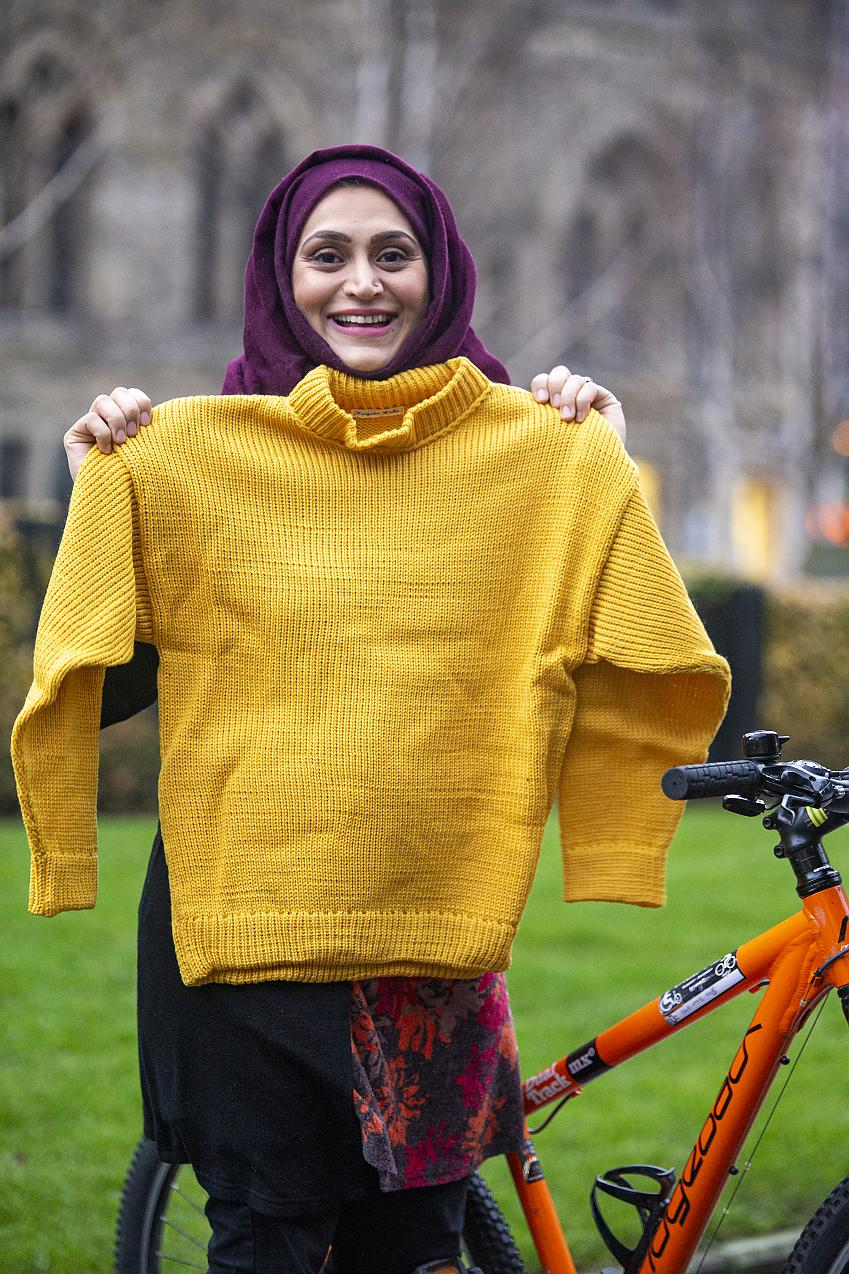A woman in a purple hijab holds up a knitted yellow sweater