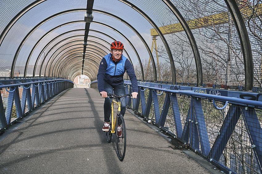A male cyclist wearing a red helmet rides across a blue bridge
